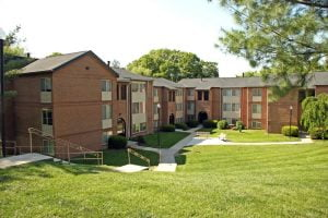 Red brick apartment complex with windows and doors completed by Acadia Windows & Doors.