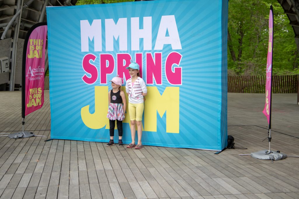 Two young girls in front of the MMHA Spring Jam sign, sponsored by Acadia Windows & Doors.